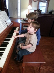 Littlest at the piano imitating Middle Boy