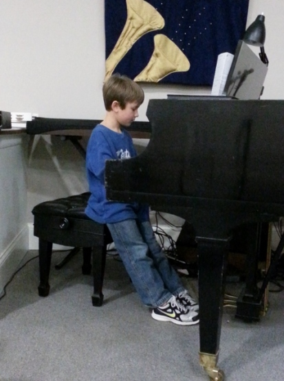 Middle Boy practicing on delightful church piano